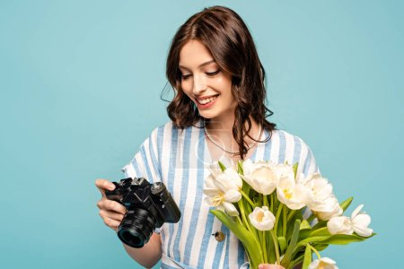Photo pour Joyeuse jeune femme tenant appareil photo numérique et bouquet de tulipes blanches isolées sur bleu - image libre de droit