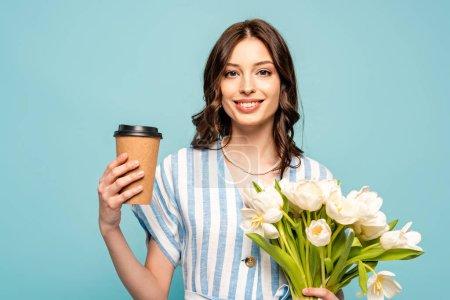 Photo pour Jolie jeune femme tenant un café pour aller et bouquet de tulipes blanches isolées sur bleu - image libre de droit