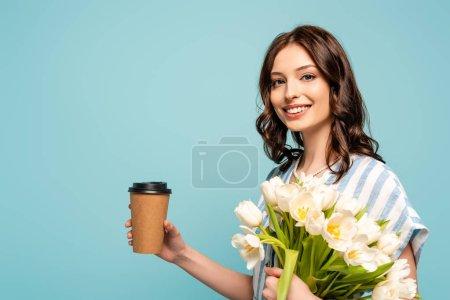 Photo pour Joyeuse jeune femme tenant du café à emporter et bouquet de tulipes blanches et regardant la caméra isolée sur bleu - image libre de droit