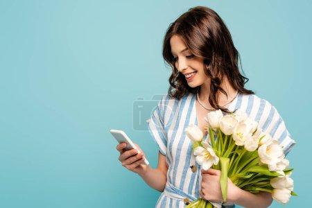 Photo pour Heureuse jeune femme bavarder sur smartphone tout en tenant les tulipes blanches isolées sur bleu - image libre de droit