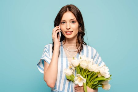 Photo for Beautiful young woman talking on smartphone while holding white tulips isolated on blue - Royalty Free Image