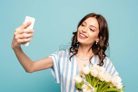 Photo pour Jeune femme heureuse prenant selfie sur smartphone tout en tenant tandis que les tulipes isolées sur bleu - image libre de droit