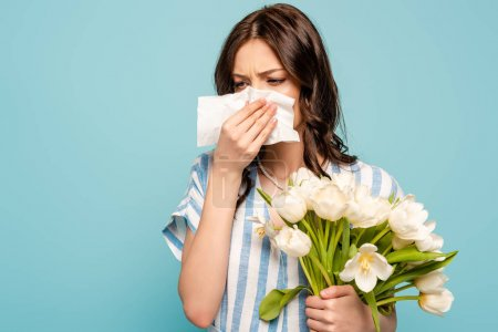 sick woman wiping nose with paper napkin while holding white tulips isolated on blue