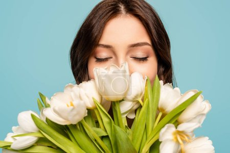 Photo for Beautiful young woman enjoying flavor of white tulips with closed eyes isolated on blue - Royalty Free Image