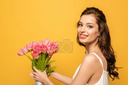 Photo for Beautiful young woman smiling at camera while holding bouquet of pink tulips isolated on yellow - Royalty Free Image