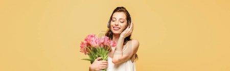 Photo pour Plan panoramique de fille heureuse écoutant de la musique dans des écouteurs sans fil tout en tenant les tulipes roses isolées sur jaune - image libre de droit