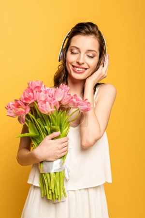 Photo for Happy young woman holding bouquet of pink tulips while listening music in wireless headphones with closed eyes isolated on yellow - Royalty Free Image