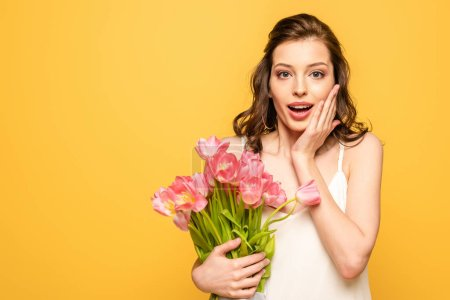 shocked young woman holding bouquet of pink tulips and touching face while looking at camera isolated on yellow