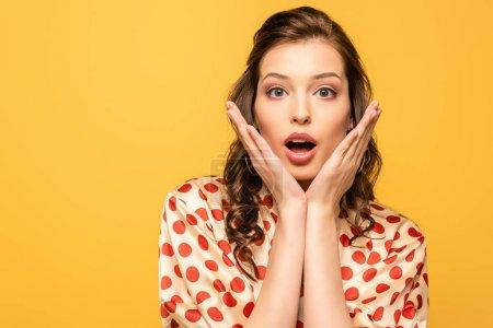 Photo pour Choqué jeune femme regardant caméra tout en tenant les mains près du visage isolé sur jaune - image libre de droit