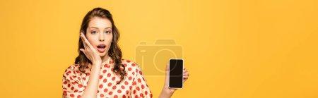 Photo pour Photo panoramique d'une jeune femme choquée qui se touche le visage en montrant un smartphone avec écran vierge isolé en jaune - image libre de droit