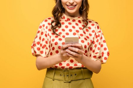 cropped view of young woman smiling while chatting on smartphone isolated on yellow