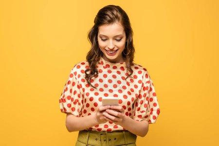 feliz joven mujer sonriendo mientras chatea en el teléfono inteligente aislado en amarillo
