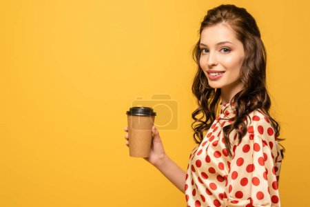 Photo for Smiling young woman holding coffee to go while looking at camera isolated on yellow - Royalty Free Image