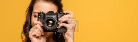 Photo pour Plan panoramique de jeune femme prenant des photos sur appareil photo numérique isolé sur jaune - image libre de droit