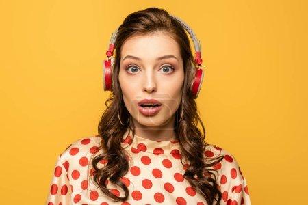 Photo pour Choqué jeune femme dans les écouteurs sans fil en regardant la caméra isolée sur jaune - image libre de droit