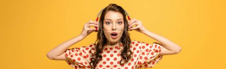 Photo pour Plan panoramique de jeune femme choquée touchant écouteurs sans fil tout en regardant la caméra isolée sur jaune - image libre de droit
