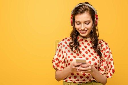 Photo pour Joyeuse jeune femme dans les écouteurs sans fil bavarder sur smartphone isolé sur jaune - image libre de droit
