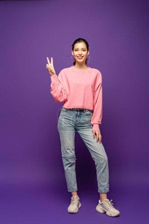 Photo pour Vue pleine longueur d'une séduisante fillette souriante à la caméra en signe de victoire sur fond violet - image libre de droit