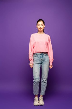 full length view of pretty, confident girl looking at camera while standing on purple background