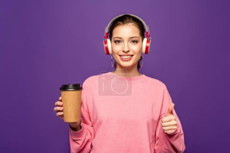 Photo for Cheerful girl holding coffee to go while listening music in wireless headphones isolated on purple - Royalty Free Image