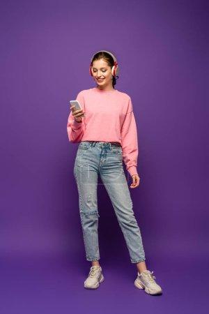 Photo pour Vue pleine longueur de jolie fille dans des écouteurs sans fil souriant tout en bavardant sur smartphone sur fond violet - image libre de droit
