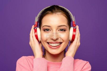 Photo pour Fille heureuse souriant à la caméra tout en touchant casque sans fil isolé sur violet - image libre de droit
