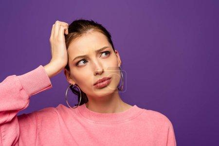 Photo pour Fille réfléchie regardant loin tout en touchant la tête isolé sur violet - image libre de droit