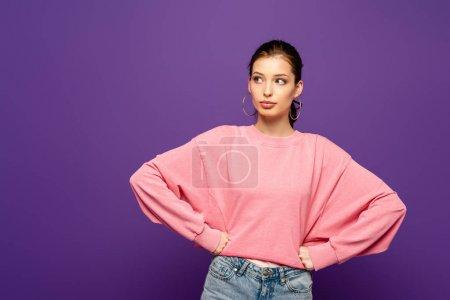 Photo pour Fille réfléchie regardant loin tout en tenant la main sur les hanches isolées sur violet - image libre de droit