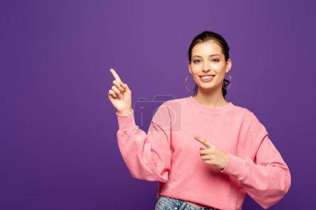 Photo pour Gaie fille souriant à la caméra tout en pointant avec les doigts isolés sur violet - image libre de droit