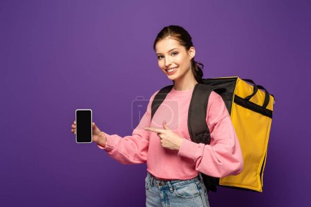 Photo pour Joli messager portant thermo box et pointant du doigt le smartphone avec écran vierge isolé sur violet - image libre de droit