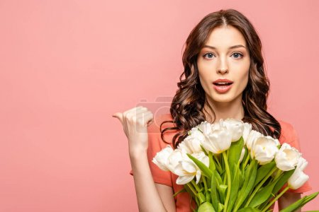 Photo for Surprised young woman looking at camera and pointing with thumb while holding white tulips isolated on pink - Royalty Free Image