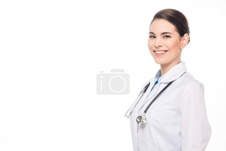 Photo for Attractive doctor in white coat and stethoscope smiling at camera isolated on white - Royalty Free Image