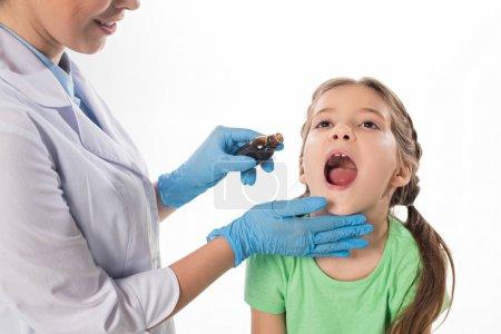 Photo pour Pediatre souriant donnant mélange à l'enfant isolé sur blanc - image libre de droit