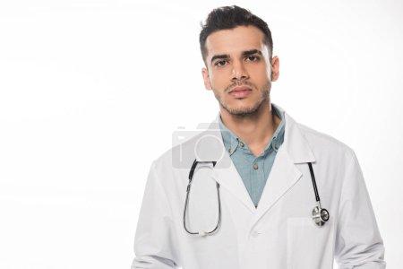 Photo pour Beau médecin en manteau blanc regardant la caméra isolée sur blanc - image libre de droit