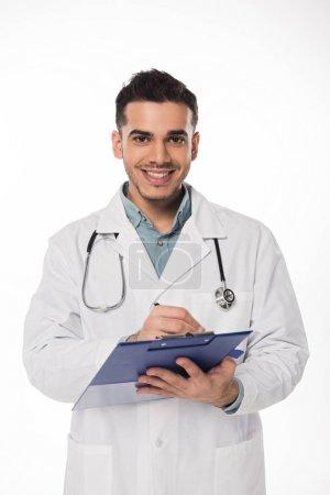 Photo pour Beau médecin souriant à la caméra écriture blanche sur presse-papiers isolé sur blanc - image libre de droit
