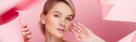Photo pour Photo panoramique d'une belle jeune wwoman au maquillage rose sur papier déchiré, sur rose - image libre de droit