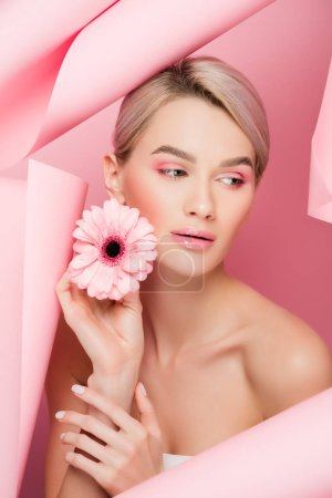 beautiful girl with pink flower and makeup in torn paper, on pink