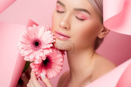 tender girl with closed eyes holding pink flowers in torn paper, on pink