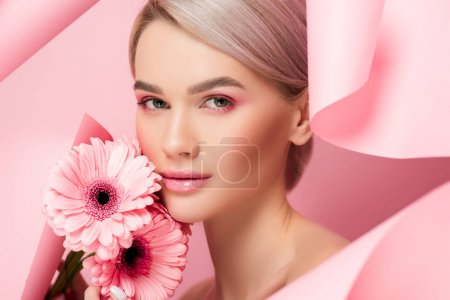 beautiful girl with pink flowers and makeup in torn paper, on pink