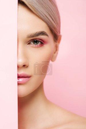 Photo pour Belle fille à la peau parfaite et au maquillage rose posant avec un morceau de papier, isolée sur rose - image libre de droit
