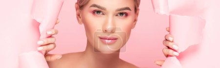 Photo for Panoramic shot of tender woman with pink makeup in torn paper, isolated on pink - Royalty Free Image