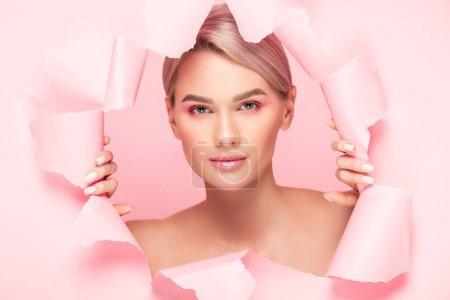 Photo pour Belle fille nue au maquillage rose dans du papier déchiré, isolée sur du rose - image libre de droit