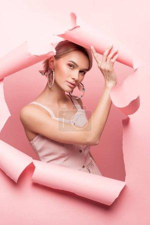 Photo pour Fille à la mode en robe rose posant en papier déchiré, en rose - image libre de droit