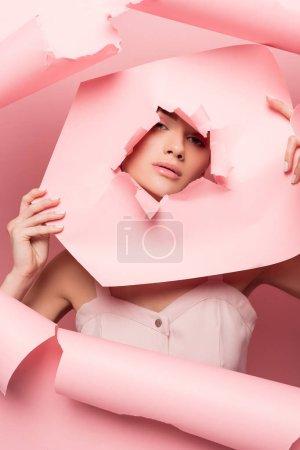 Photo pour Jolie femme stylisée en robe rose posant avec du papier déchiré, en rose - image libre de droit