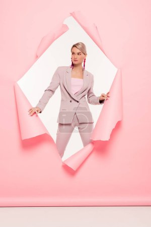 Photo for Fashionable girl in trendy suit posing in torn paper, on white - Royalty Free Image