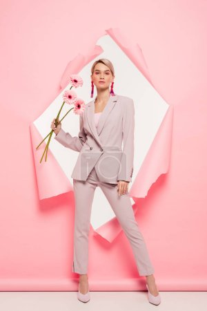 Photo for Beautiful girl in fashionable suit holding flowers and posing in torn paper, on white - Royalty Free Image
