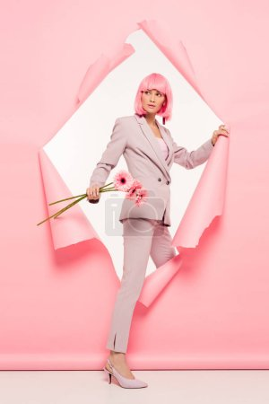 stylish woman in suit and pink wig holding flowers and posing in torn paper, on white