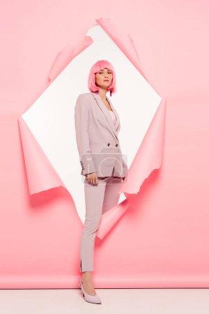 Photo pour Belle fille à la mode en costume et perruque rose posant en papier déchiré, sur blanc - image libre de droit
