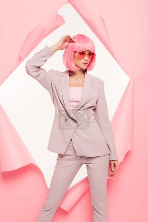 Photo for Stylish girl in suit, sunglasses and pink wig posing in torn paper, isolated on white - Royalty Free Image