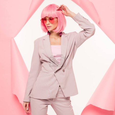 Photo for Fashionable girl in suit, sunglasses and pink wig posing in torn paper,  isolated on white - Royalty Free Image